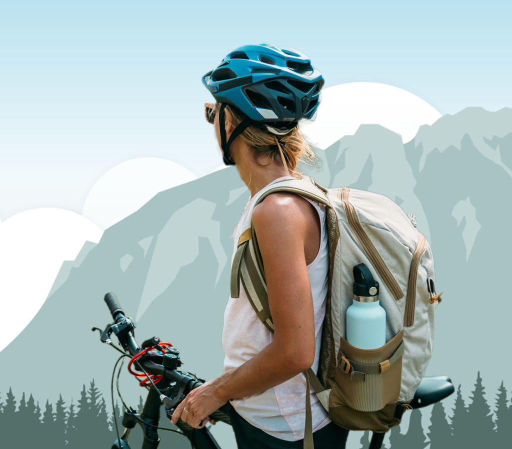 Woman with mountain bike in front of illustrated mountains