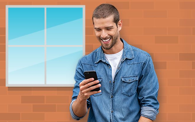 Man smiling at his phone in front of brick building with window